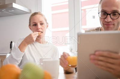 Couple sits at a table eating and looking at a pc