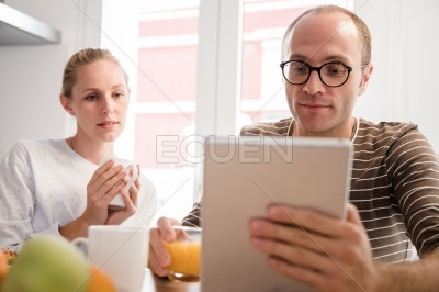 Couple sitting at a table looking at a pc tablet
