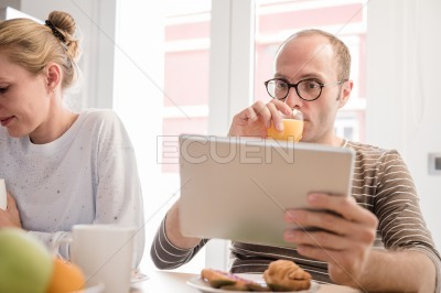 Man sitting at a table drinking a glass of juice