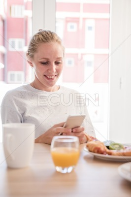 Woman at a breakfast table looking at a cell phone