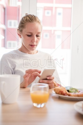 Woman at a table texting from a cell phone
