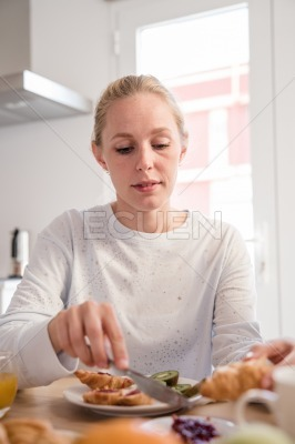 Woman butters a croissant with jam at a table