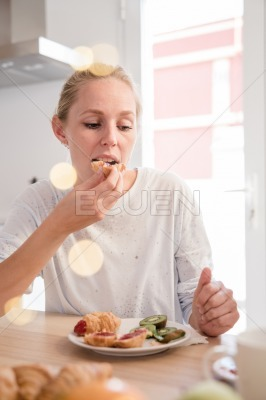 Woman eats a croissant as she sits at a table