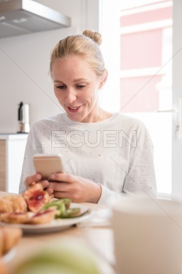Woman looking down at her phone and smiling