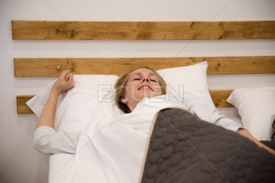 Woman lying in bed and stretching