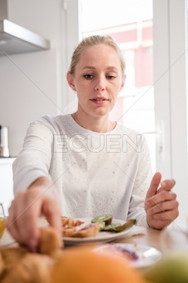 Woman reaches for a croissant at a table