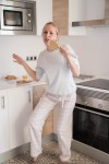 Blonde woman in a kitchen dancing and singing