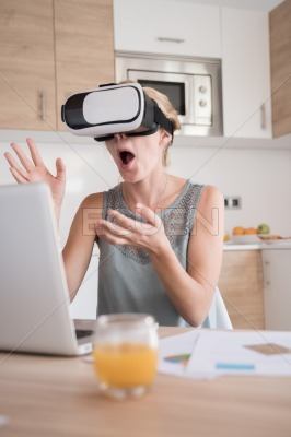 Woman gasping as she wears virtual reality glasses