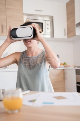 Woman holds virtual reality glasses to her face