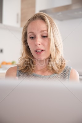 Woman looking at a pc laptop with raised eyes
