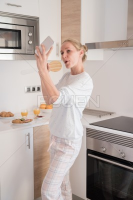 Woman singing in the kitchen as she takes a selfie