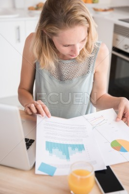 Woman sitting at a table reading documents