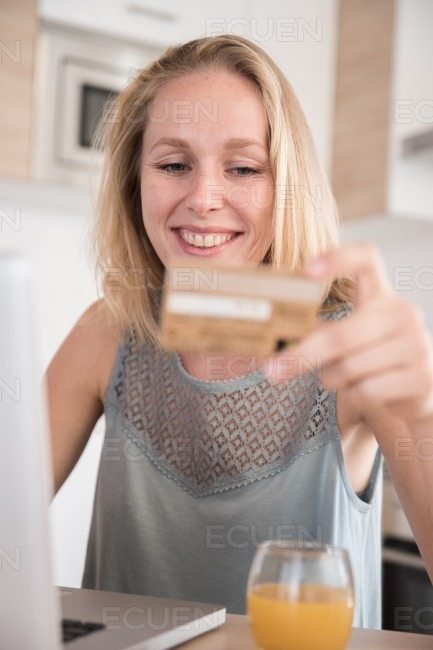 Woman smiling at a credit card at her laptop