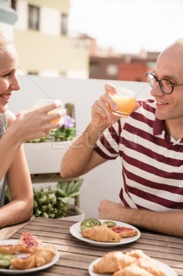 Couple drinking glasses of juice at a table