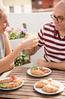 Couple toasting each other at a table