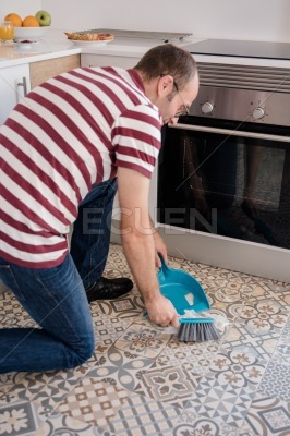 Man bending a sweeping a floor