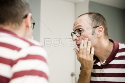 Reflective image of a man looking into a mirror
