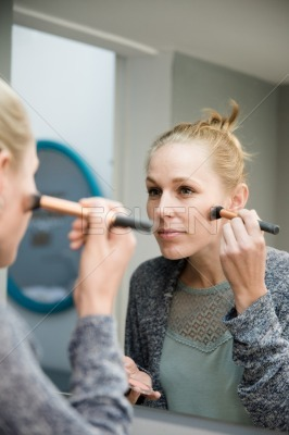 Woman applying makeup in front of a mirror