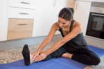 Close up of a woman stretching on a mat