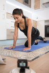 Woman leaning forward and she kneels on a mat