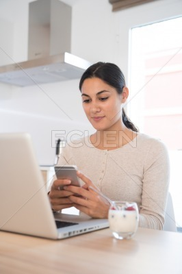 Woman looking at a cell phone as she sits