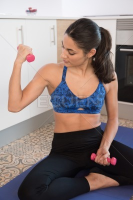Woman sits on the floor holding exercise weights