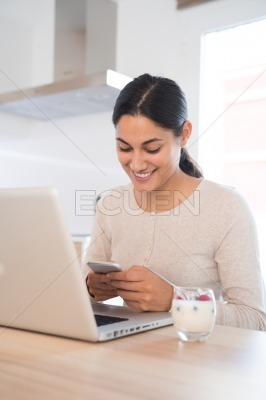 Woman texting and smiling on a cell phone