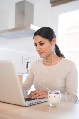 Woman typing on a laptop pc at a table