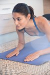 Woman doing a push up on a blue mat