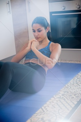 Woman doing stomach crunches on a blue mat