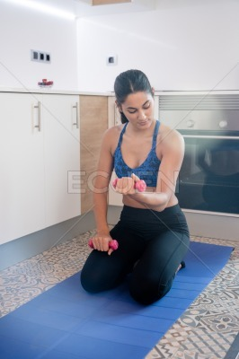 Woman holding a weight as she loops at her bicep