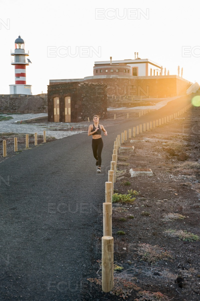 Woman running on a black tarred road with poles stock photo