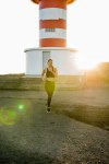 Woman running with a lighthouse in the background