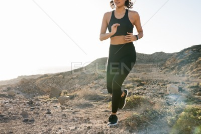 Torso short of a woman s midsection as she runs
