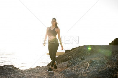 Woman in gym clothes walking along the shoreline
