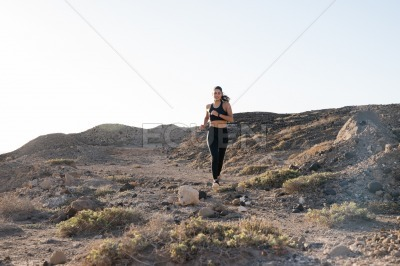 Woman jogging in the desert along a rocky path