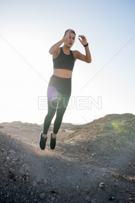 Woman jumping up in the air with straight legs
