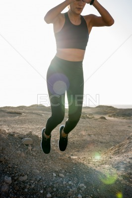 Woman jumping with her hands above her head