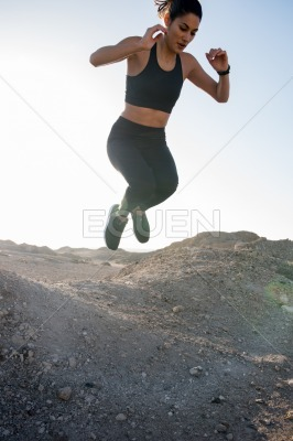 Woman jumping with her legs curled under her