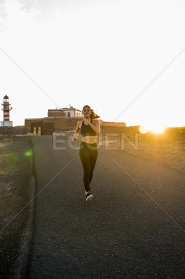 Woman running along a road as the sun sets
