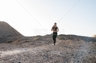 Woman running along a rocky path with stones