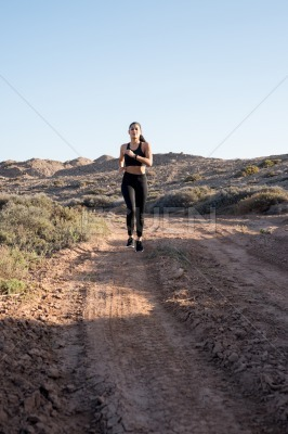 Woman running on a dirt road in the sun