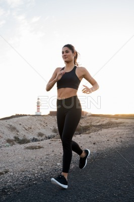 Woman running on a sand road past a lighthouse