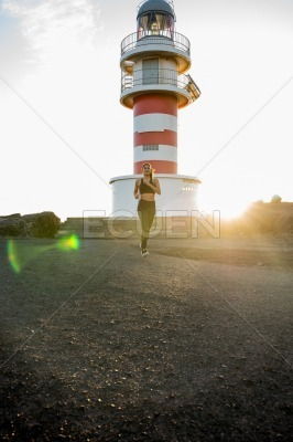 Woman running past a lighthouse as the sun sets