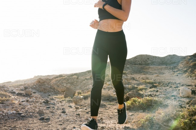 Close up of a midriff of a young woman running
