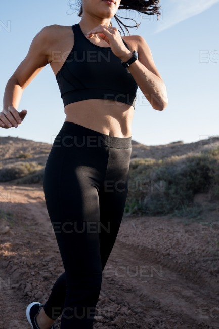 Close up of woman in black running gear running stock photo