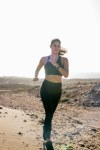 Woman sprinting as she runs in the desert