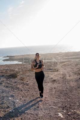 Woman running on a grassy and sandy road