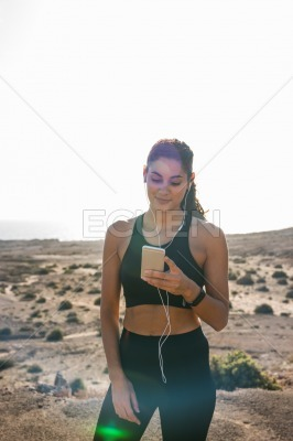 Woman standing in the desert holding a cell phone