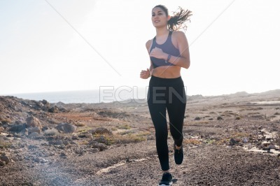 Young woman running as her hair swings in the wind